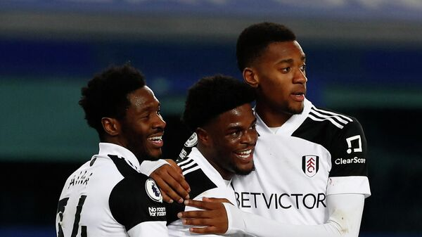 Fulham's Nigerian defender Ola Aina (L) and Fulham's English defender Tosin Adarabioyo (R) congratulate Fulham's Nigerian striker Josh Maja as he celebrates scoring his team's second goal during the English Premier League football match between Everton and Fulham at Goodison Park in Liverpool, north west England on February 14, 2021. (Photo by JASON CAIRNDUFF / POOL / AFP) / RESTRICTED TO EDITORIAL USE. No use with unauthorized audio, video, data, fixture lists, club/league logos or 'live' services. Online in-match use limited to 120 images. An additional 40 images may be used in extra time. No video emulation. Social media in-match use limited to 120 images. An additional 40 images may be used in extra time. No use in betting publications, games or single club/league/player publications. /