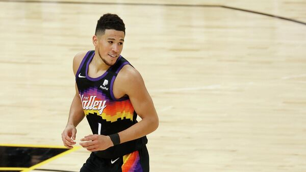 PHOENIX, ARIZONA - FEBRUARY 13: Devin Booker #1 of the Phoenix Suns reacts after a three-point shot against the Philadelphia 76ers during the second half of the NBA game at Phoenix Suns Arena on February 13, 2021 in Phoenix, Arizona. The Suns defeated the 76ers 120-111. NOTE TO USER: User expressly acknowledges and agrees that, by downloading and or using this photograph, User is consenting to the terms and conditions of the Getty Images License Agreement.   Christian Petersen/Getty Images/AFP