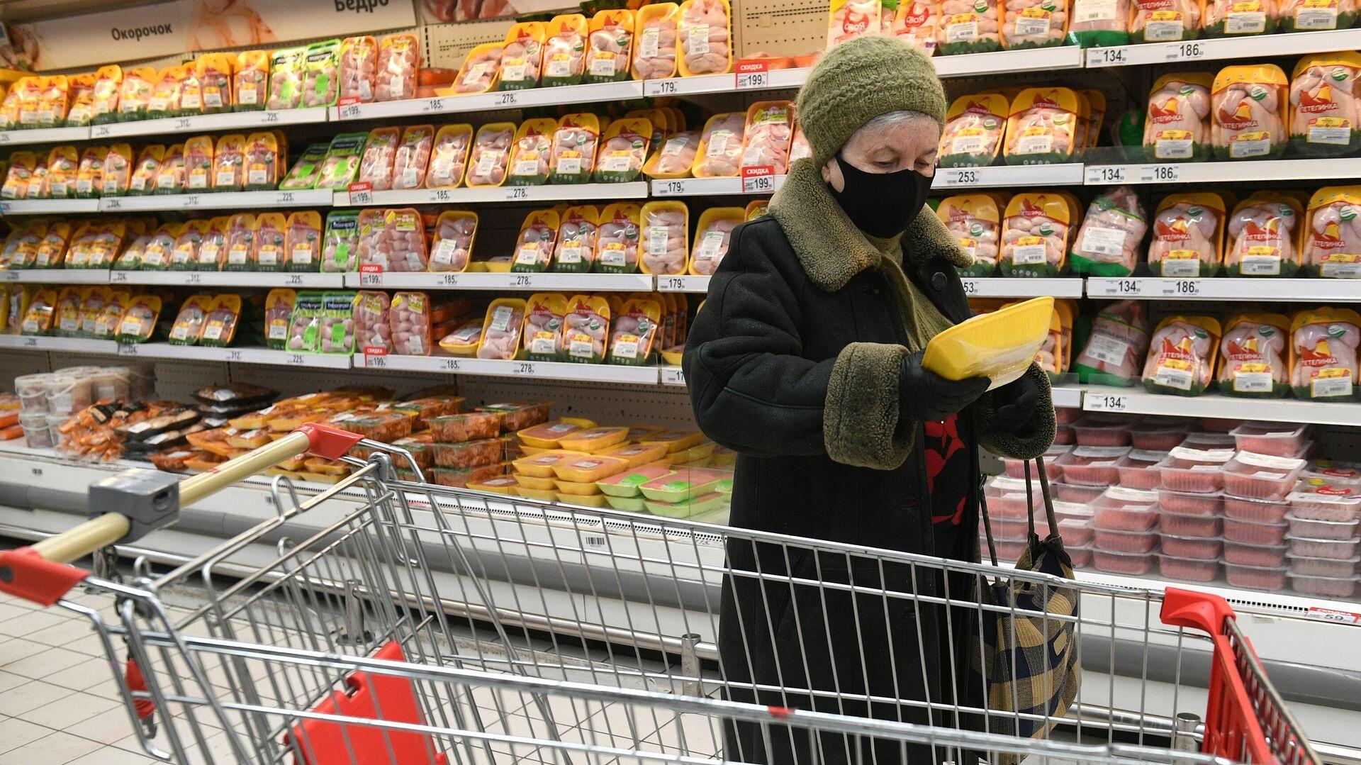 Покупательница выбирает курицу в мясном отделе гипермаркета Ашан в Москве - РИА Новости, 1920, 04.03.2021