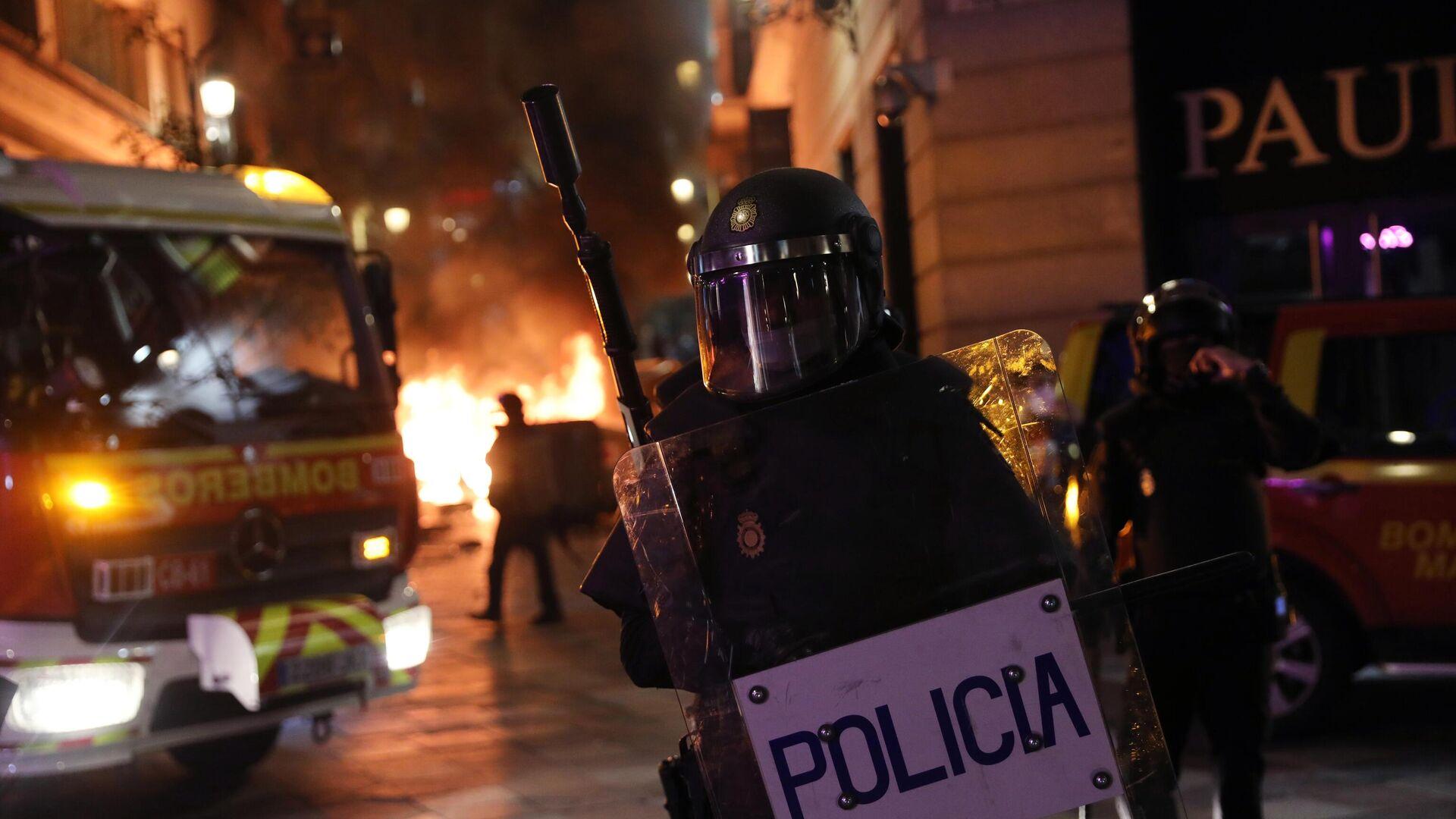 Сотрудник полиции во время акции протеста в поддержку рэпера Пабло Аселя, приговоренного к девяти месяцам заключения за оскорбление монархии и прославление леворадикального терроризма, на площади Пуэрта-дель-Соль в Мадриде - РИА Новости, 1920, 18.02.2021
