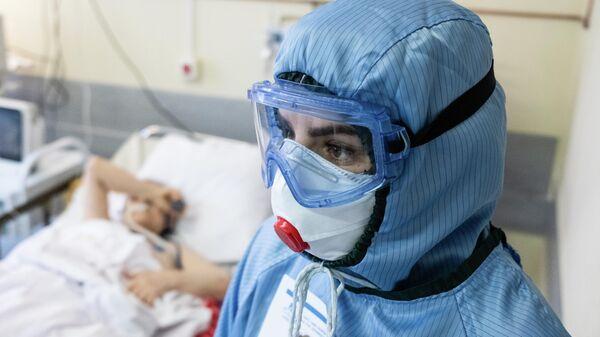 Медицинский работник и пациент c COVID-19 в НИИ скорой помощи им. Н. В. Склифосовского в Москве