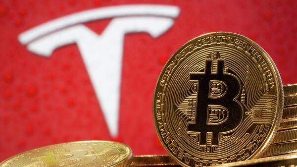 Криптовалюта биткоин на фоне иллюстрации с логотипом Tesla