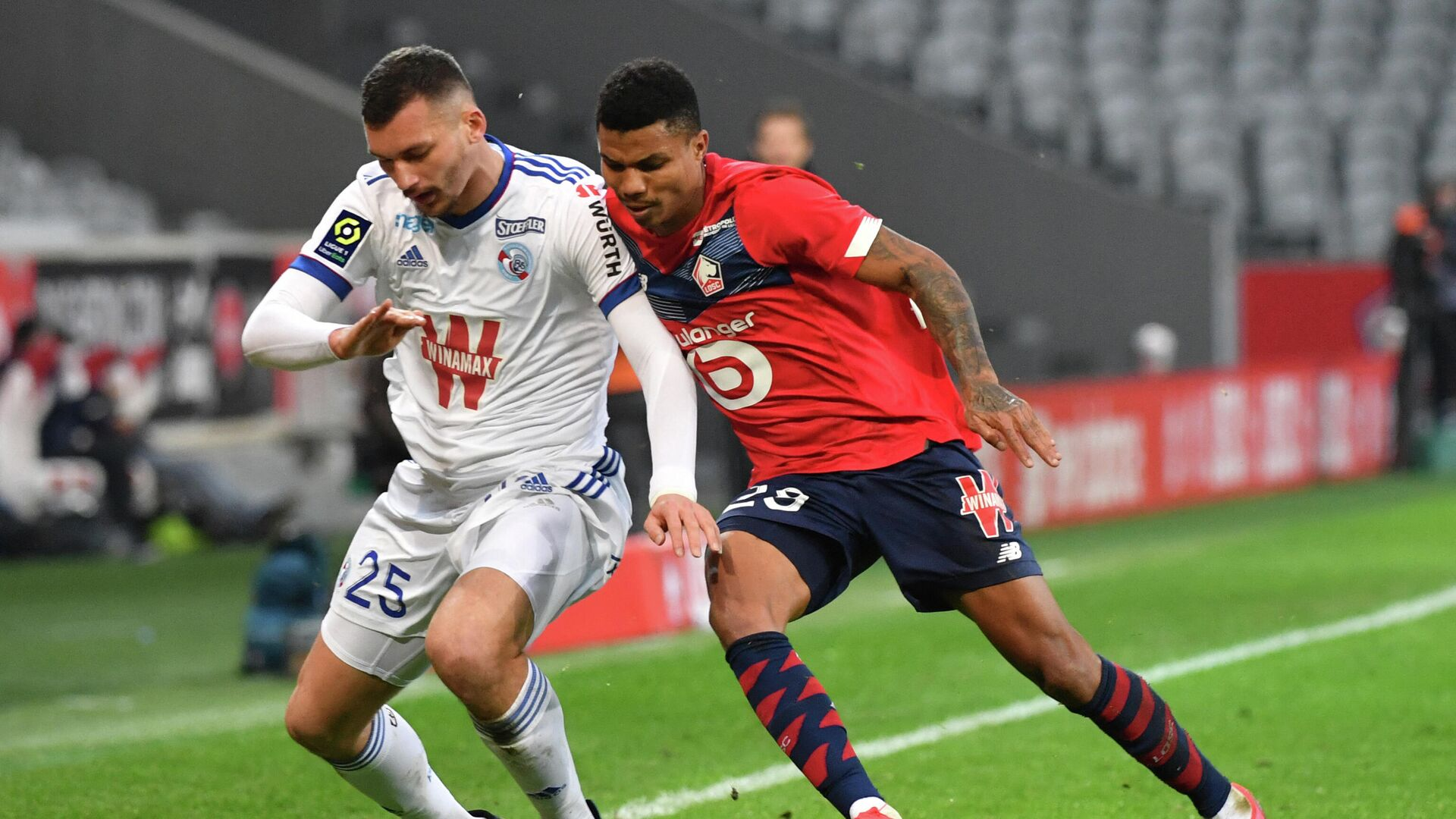 Lille's Mozambican defender Reinildo Mandava (R) fights for the ball with Strasbourg's French forward Ludovic Ajorque during the French L1 football match between Lille LOSC and Racing Club Strasbourg Alsace at the Pierre-Mauroy stadium in Villeneuve-d'Ascq, near Lille, northern France on February 28, 2021. (Photo by DENIS CHARLET / AFP) - РИА Новости, 1920, 28.02.2021