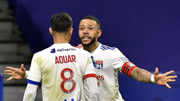 Lyon's French midfielder Houssem Aouar (L) celebrates with Lyon's Dutch forward Memphis Depay after scoring during the French L1 football match between Olympique Lyonnais and Stade Rennais Football Club at the Groupama Stadium in Decines-Charpieu, near Lyon, central-eastern France on March 3, 2021. (Photo by PHILIPPE DESMAZES / AFP)