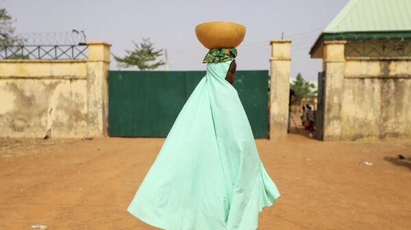 Девушка с чашей молока у ворот школы в Нигерии, где были похищены более 300 учениц