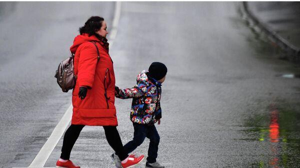 Женщина с ребенком идут по пешеходному переходу
