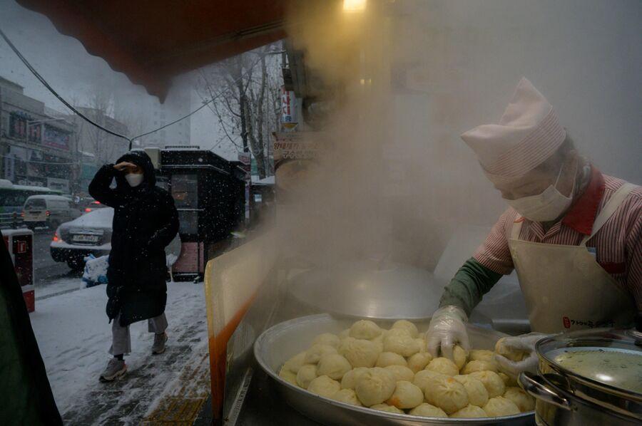 Уличный торговец готовит дамплинги в Сеуле, Южная Корея