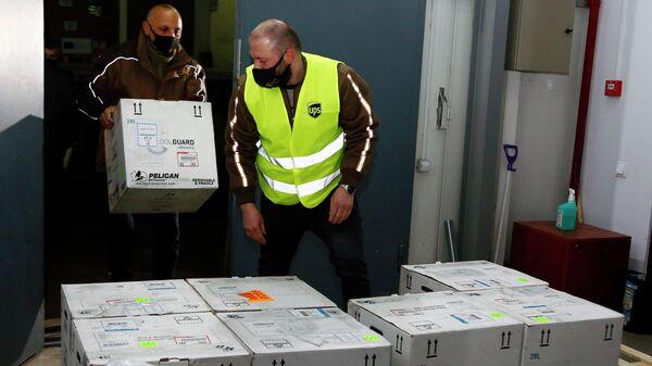 Сотрудники разгружают коробки с вакцинами от COVID-19, разработанными компанией Pfizer в Тбилиси