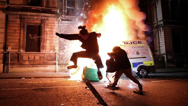Демонстрант катается на скейтборде перед горящей полицейской машиной во время акции протеста против нового законопроекта о полиции, Бристоль, Великобритания