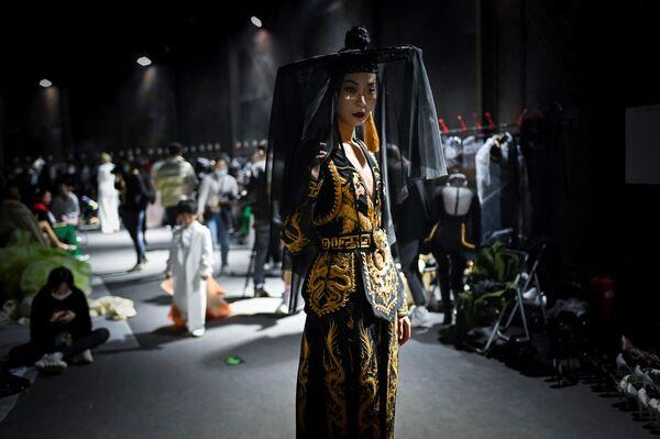 Модель в наряде марки Xiong Ying перед показом на Китайской неделе моды в Пекине