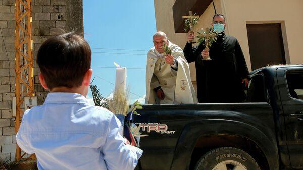 Священник посещает районы в Южном Ливане, чтобы благословить верующих во время Пальмового воскресенья