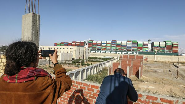 Люди фотографируют контейнеровоз Ever Given, покидающий Суэцкий канал