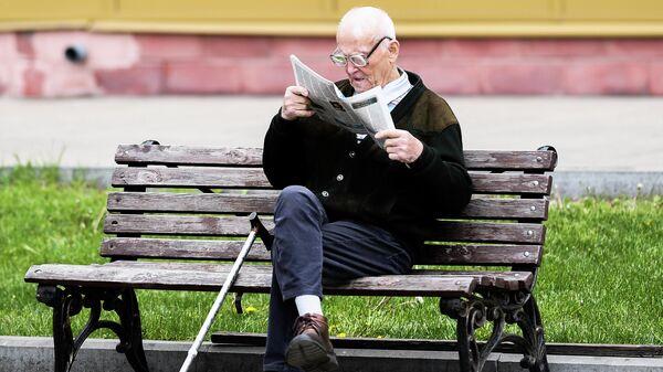 Мужчина читает газету на улице на лавочке в Москве