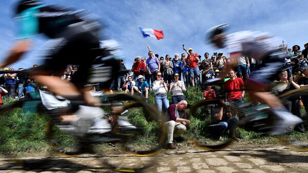(FILES) In this file photo taken on April 8, 2018 spectators watch cyclists as they drive across cobbled stone during the 116th edition of the Paris-Roubaix one-day classic cycling race, between Compiegne and Roubaix, in Quievy, northern France. - The International Cycling Union (UCI) announced on April 1, 2021, that Paris-Roubaix, the queen of classics, cycle race has been postponed from April 11 to October 3 because of the ongoing coronavirus (Covid-19) pandemic. (Photo by JEFF PACHOUD / AFP)