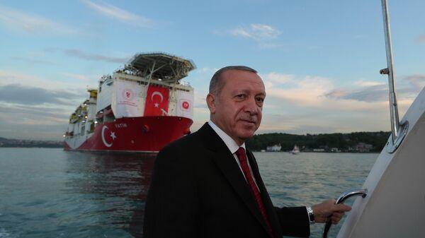 Президент Турции Реджеп Тайип Эрдоган на фоне турецкого корабля Фатих, проходящего пролив Босфор в Стамбуле