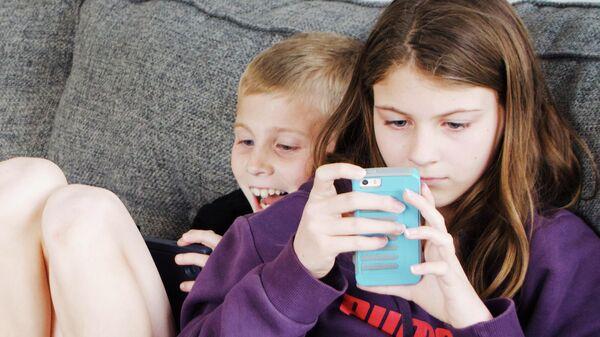 Дети с мобильными телефонами в руках