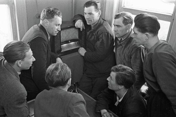 Рабочие совхоза Заокский слушают сообщение по радиоприемнику о полете космического корабля Восток-1 с  космонавтом Юрием Алексеевичем Гагариным на борту