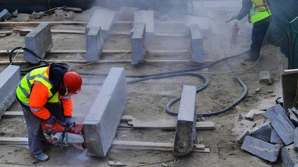 Рабочие во время реставрации гранита с Большого Каменного моста на территории строительной компании Лазурит в Троицке