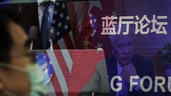 Мужчина возле экрана, демонстрирующего, встречу делегатов Китая и США на форуме Лантинга