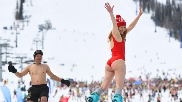 Участники массового спуска в купальниках в рамках фестиваля GrelkaFest на горнолыжном курорте в поселке Шерегеш Кемеровской области