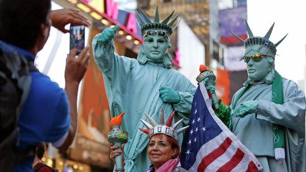 Туристы фотографируются с мужчинами, одетым в костюмы Статуи Свободы, на Таймс-сквер в Нью-Йорке, США