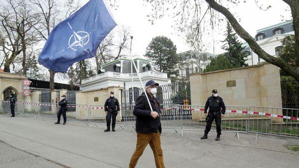 Мужчина с флагом НАТО напротив Российского посольства в Праге, во время акции протеста, связанной с объявленной причастностью России ко взрывам на складах боеприпасов в деревне Врбетице в 2014 году