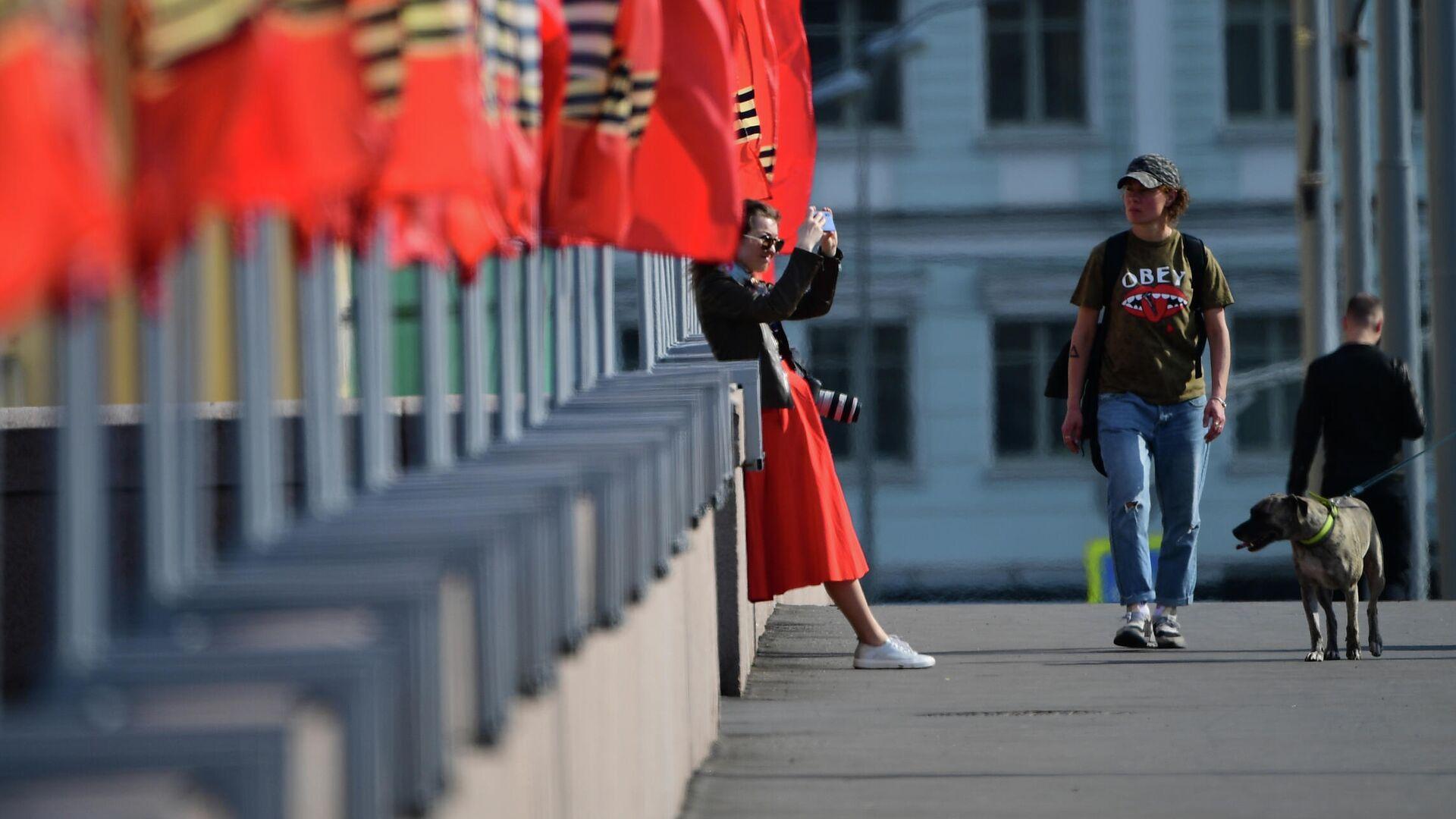 Девушка фотографируется у флагов, установленных к празднованию Дня Победы, на Москворецкой набережной в Москве - РИА Новости, 1920, 10.05.2021