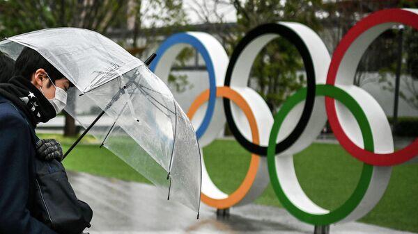 Житель Токио гуляет рядом с японским Олимпийским музеем в Токио