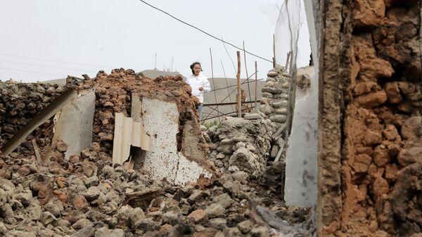 Девушка стоит у разрушенного строения в приграничном с Таджикистаном селе Кок-Таш
