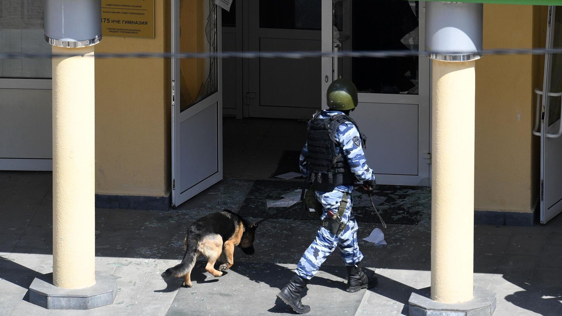 Сотрудник правоохранительных органов со служебной собакой у школы в Казани, где произошла стрельба - РИА Новости, 1920, 11.05.2021