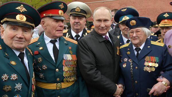 Президент РФ Владимир Путин фотографируется с ветеранами после церемонии возложения цветов к Вечному огню у Могилы Неизвестного Солдата в Александровском саду