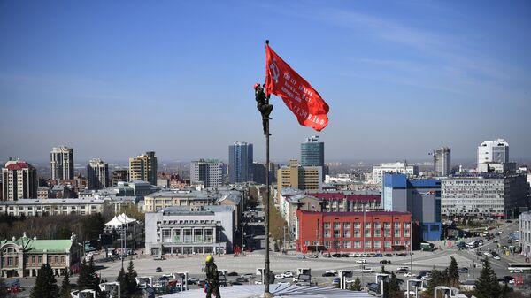 Промышленные альпинисты во время установки копии Знамени Победы над куполом НОВАТ в центре Новосибирска