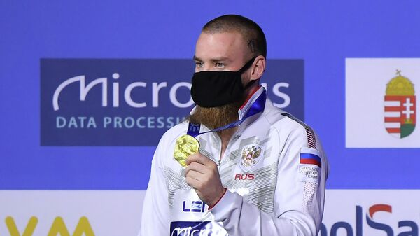 Gold medallist Russia's Evgenil Kuznetsov poses on the podium  after the Men's 3m Springboard Diving event during the LEN European Aquatics Championships at the Duna Arena in Budapest on May 14, 2021. (Photo by Attila KISBENEDEK / AFP)