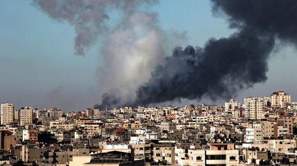 Дым поднимается на месте зданий, разрушенных израильским авиаударом в городе Газа