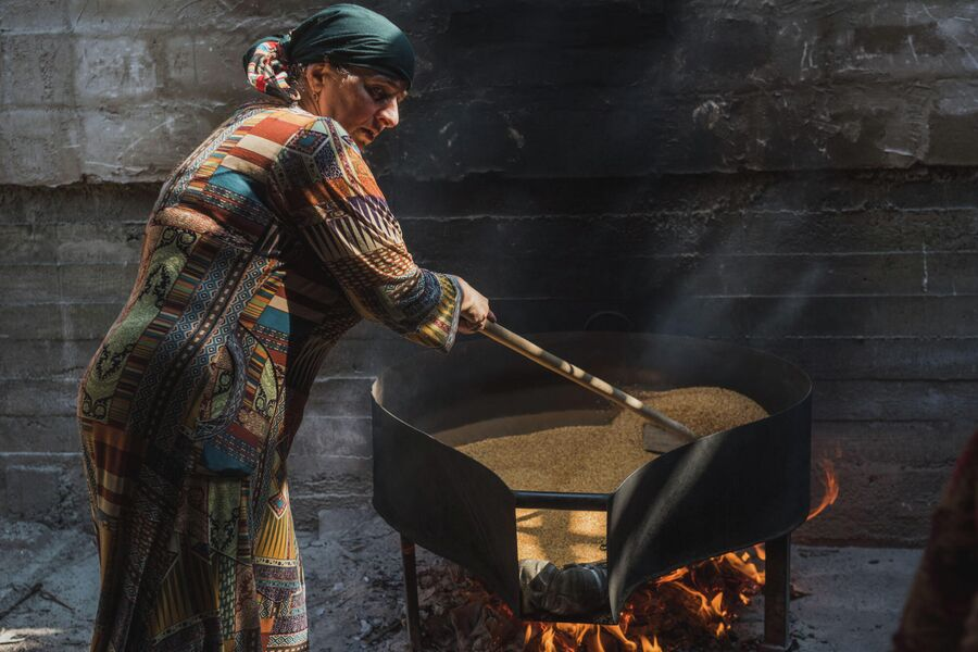 Женщина поджаривает семена льна для приготовления урбеча на водяной мельнице. Село Рахата, Ботлихская долина
