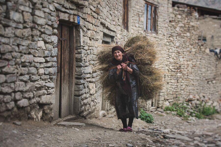 Женщина несет стено через село Корода