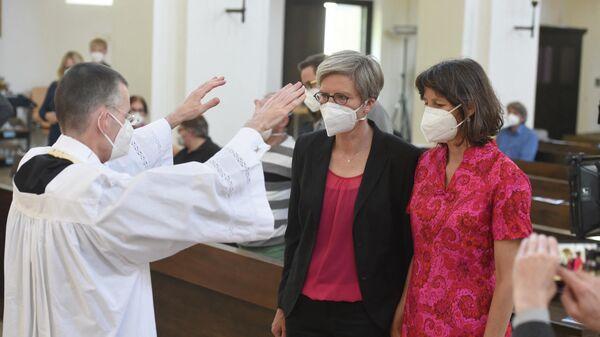 Священник благословляет однополую пару в церкви Святого Бенедикта в Мюнхене, Германия