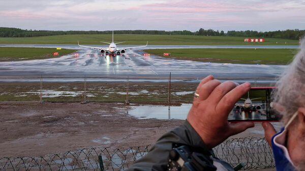 Женщина фотографирует посадку самолета авиакомпании Ryanair  в Вильнюсе