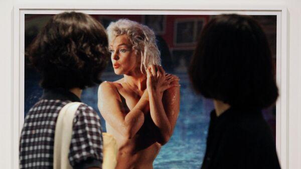 Посетители смотрят на фотографию Мэрилин Монро во время фотовыставки в Сеуле