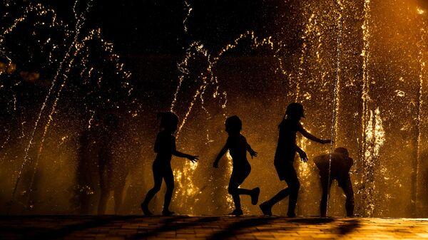 Дети играют в фонтане