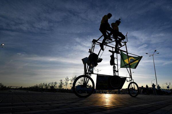 Бразильские футбольные фанаты катаются на самодельном трехметровом тандемном велосипеде возле Ростов-Арены накануне матча между Бразилией и Швейцарией во время чемпионата мира по футболу