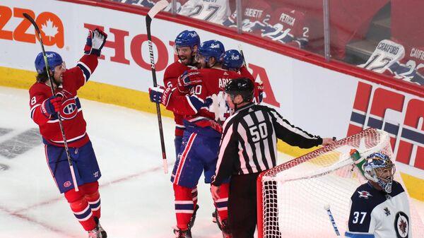 Хоккеисты Монреаль Канадиенс празднуют заброшенную шайбу в матче с Виннипег Джетс.