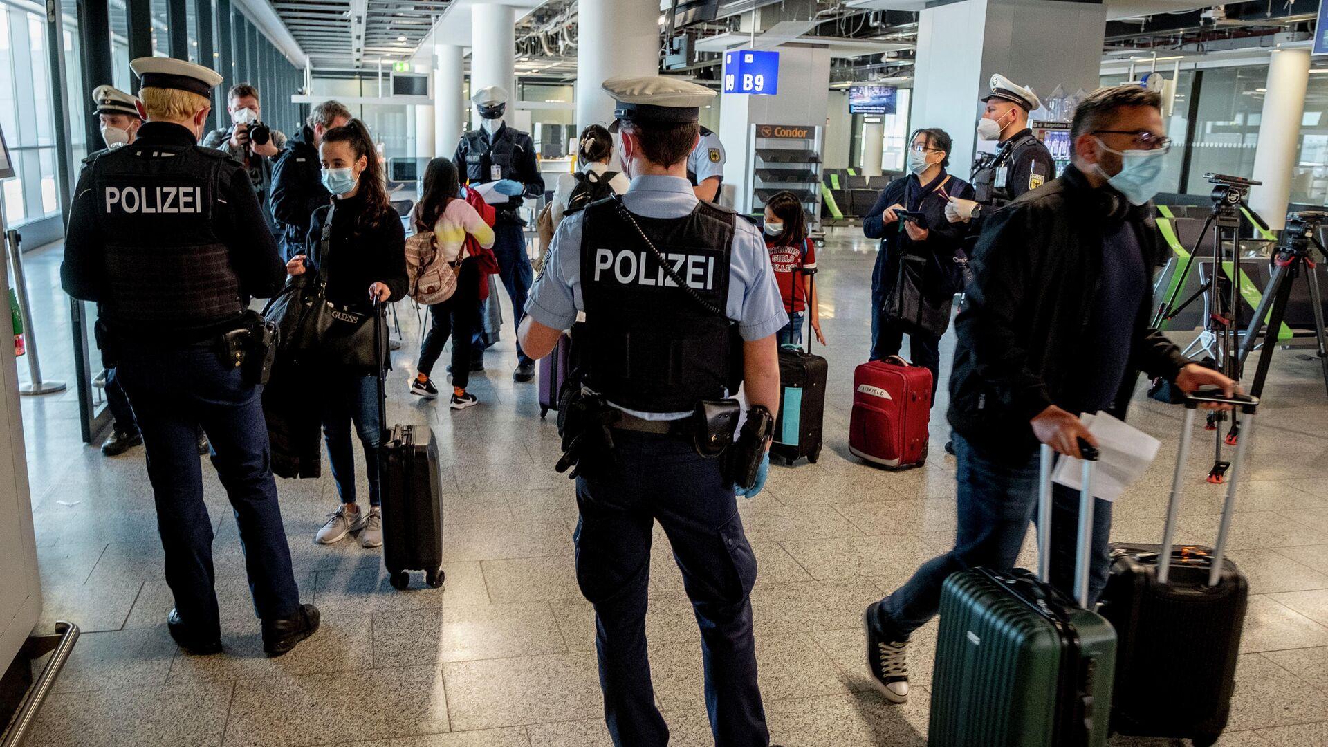 Сотрудники полиции проверяют наличие теста на коронавирус у прибывших пассажиров в аэропорту Франкфурта, Германия - РИА Новости, 1920, 12.07.2021