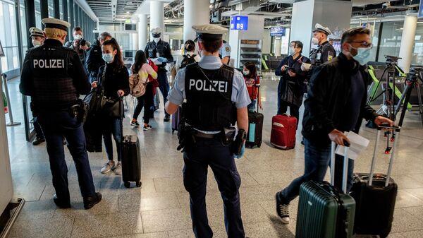 Сотрудники полиции проверяют наличие теста на коронавирус у прибывших пассажиров в аэропорту Франкфурта, Германия