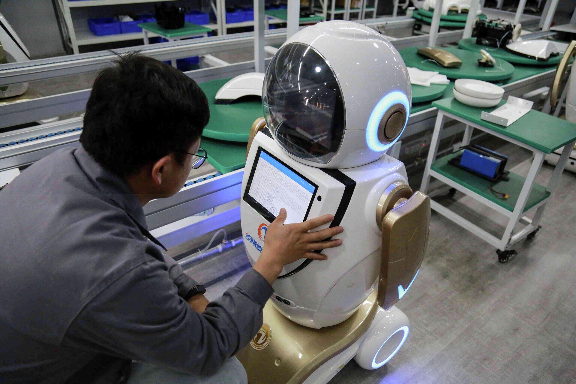 Рабочий проверяет робота, предназначенного для экспорта на Ближний Восток, на фабрике в Чжанъе - РИА Новости, 1920, 10.06.2021