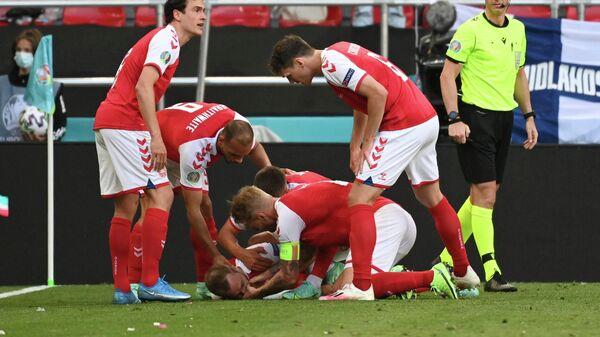 Игроки сборной Дании оказывают помощь потерявшему сознание Кристиану Эриксену.