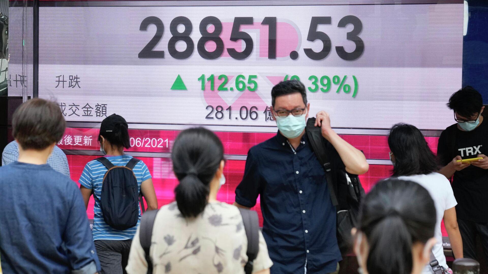 Люди в защитных масках проходят мимо табло с котировками ценных бумаг в Гонконге - РИА Новости, 1920, 22.07.2021