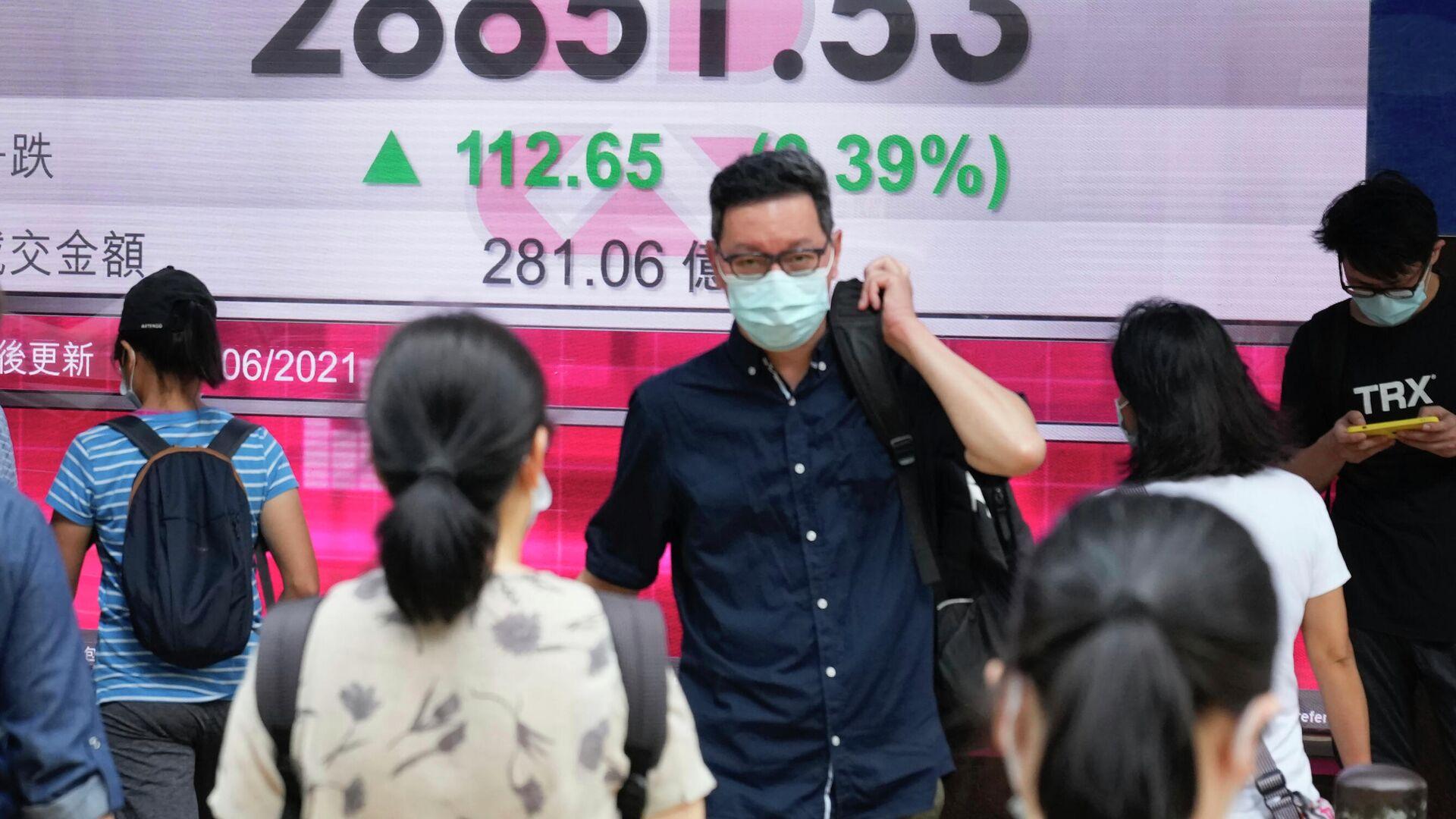 Люди в защитных масках проходят мимо табло с котировками ценных бумаг в Гонконге - РИА Новости, 1920, 19.07.2021