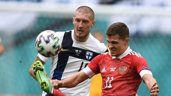 Игрок сборной России Роман Зобнин (справа) и игрок сборной Финляндии Йони Кауко в матче 2-го тура группового этапа чемпионата Европы по футболу 2020 между сборными Финляндии и России.