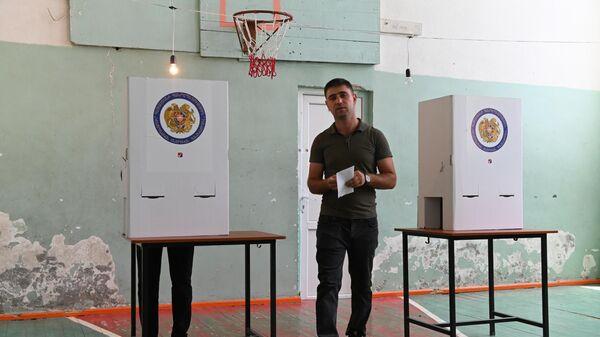 Мужчина голосует на одном из избирательных участков в Ереване во время досрочных парламентских выборов в Армении